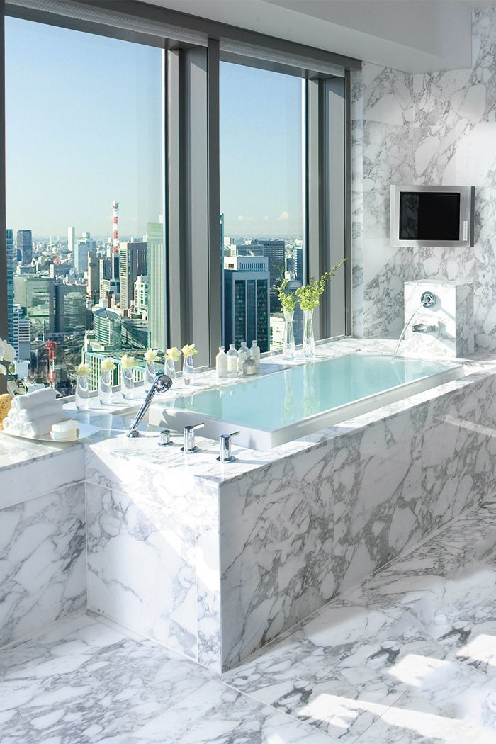 infinity tub surrounded by marble looking out on a beautiful city view and if you get bored with that thereu0027s always a like the marble tbh