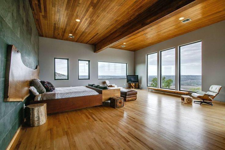 Eine Holzdecke und Bodenbelag begibt dramatisch sich dieser geräumige Schlafzimmer.