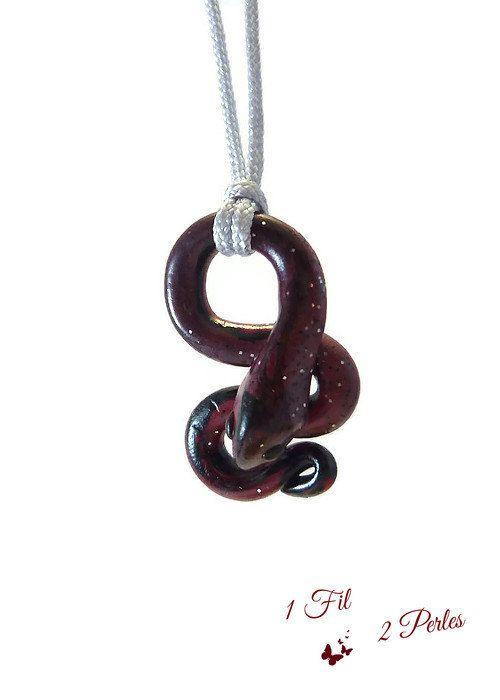 Le Pendentif Serpent SNAKE LUCKY petit modèle est fabriqué par 1 Fil 2 Perles dans son atelier.  Le Serpent en Argile Polymère est obtenu par mélange de couleurs, ici du Rouge et du Noir pailleté. Chaque pièce est unique, leur forme, grandeur et position varient à chaque modèle.  Le serpent est un reptile, symbole dimmortalité et de sagesse, posé sur votre cou il attirera forcément les regards. Il mesure 3 cm de haut x 2 cm de large (au plus fort). Le cordon en nylon gris brillant avec un…