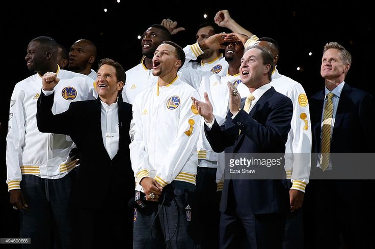 Stephen Curry #30 of the Golden State Warriors celebrates with owners (left) Peter Guber and (right) Joe Lacob as their 2015 championship banner is unveiled prior to their game against the New Orleans Pelicans in the NBA season opener at ORACLE Arena on October 27, 2015 in Oakland, California.