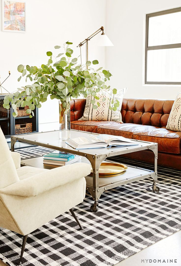 Living room with brown leather couch, patterned pillows, white walls, large plants, colorful artwork, silver coffee table, black and white checkered rug, white chair and brass floor lamp: