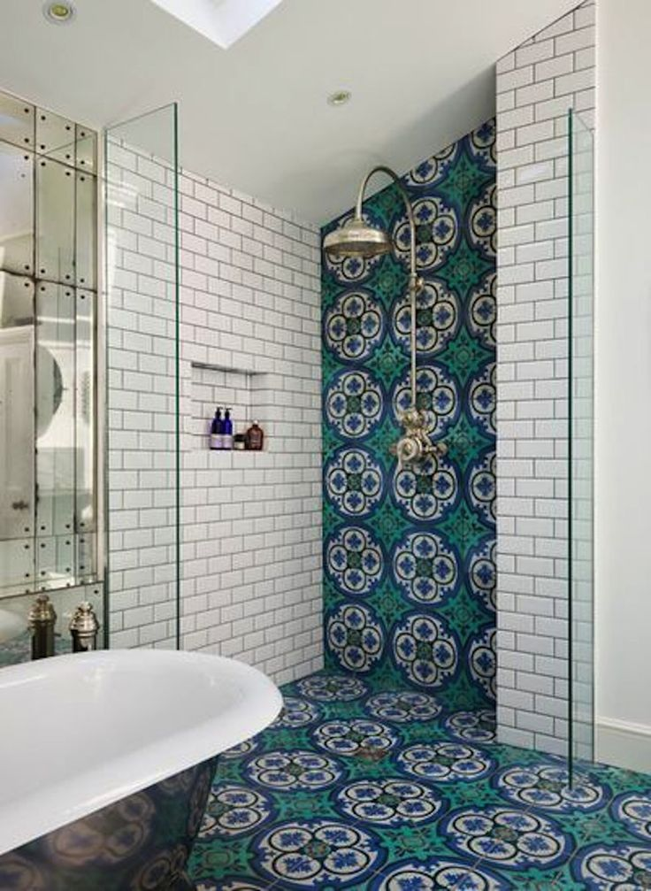 vibrant teal turquoise and blue patterned tiles line the wall from floor to ceiling create a channel for the shower