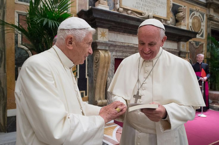 This handout picture released by the Vatican press office shows Pope Francis (R) during a celebration to mark the 65th anniversary of the ordination of Pope Emeritus Benedict XVI (R) on June 28, 2016 at the Vatican. Three years after he became the first pope to retire in seven centuries, the 89-year-old German confounded rumours that his health was failing by standing for nearly ten minutes as he spoke in a clearly audible, steady voice in a mixture of Italian and Latin.  / AFP PHOTO…