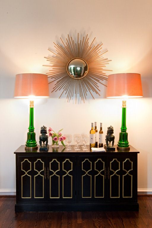 Hollywood Regency & symmetrical glamour. Love the emerald lamps and gold sunburst mirror.