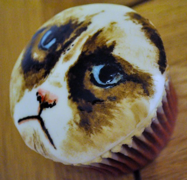 Grumpy Cat Cupcake. Jenni Powell of Two Little Cats Bakery painted the sweet but sour-faced likeness of Tard the Grumpy Cat on a cupcake.