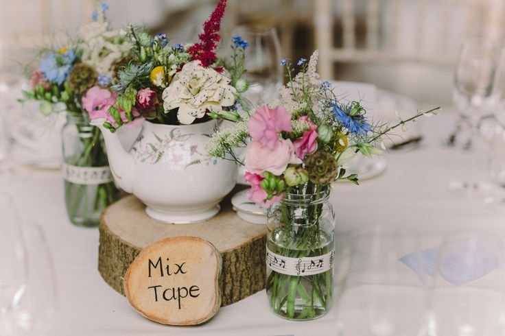 Rustic tree slab and tea pot with flowers - Image by Charli Photography - Lusan Mandongus Lace Dress for a rustic wedding in barn with musical theme and pastel colour scheme.