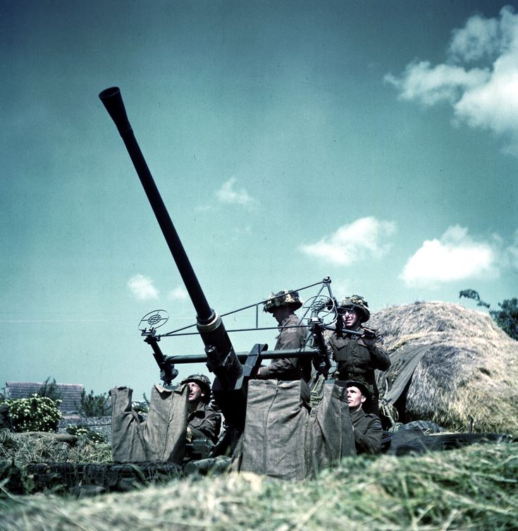Canadian soldiers manning a 40-mm Bofors anti-aircraft gun in Normandy, France, Jun 1944.