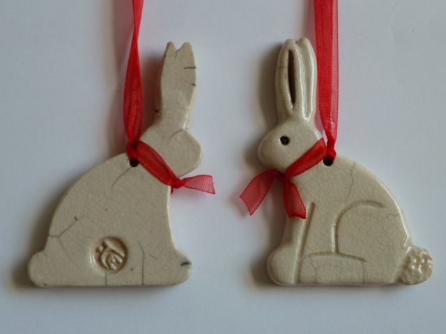 Little white rabbits in Raku with red bow and hung with red ribbon
