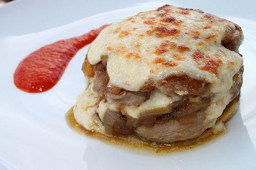 Solomillo de cerdo con patatas, cebolla confitada, queso y Coulís de pimientos del piquillo.