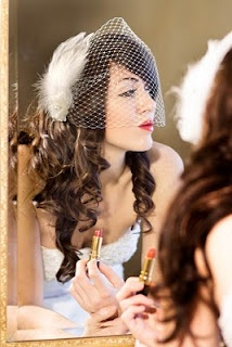 Lover her long curls and bandeau birdcage veil with feather fascinator.