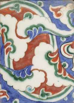 AN IZNIK POTTERY TILE   OTTOMAN TURKEY, CIRCA 1590   Of rectangular form, with cusped palmettes in bole red and green over cobalt-blue ground, framed