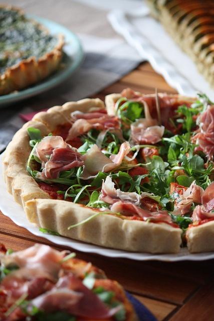 Pizza fraîcheur : on fait cuire d'abord la pâte avec la sauce tomate et les tranches de mozza, puis on recouvre de roquette et lamelles de jambon