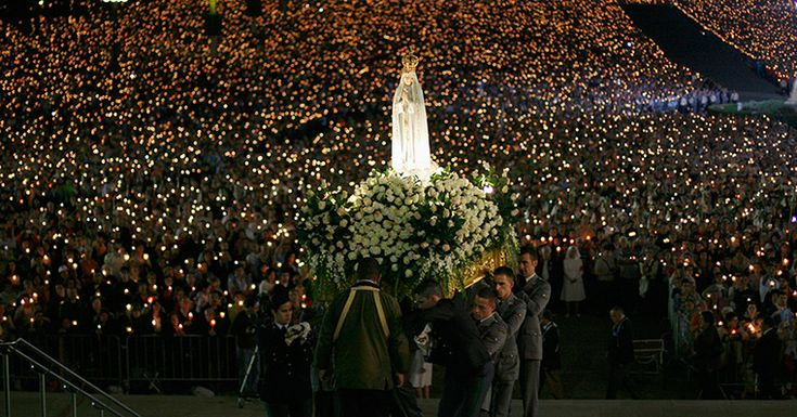 Fatima, Portugal: A statue of the Holy Virgin Mary of Fatima is carried during a candlelight vigil at the holy shrine