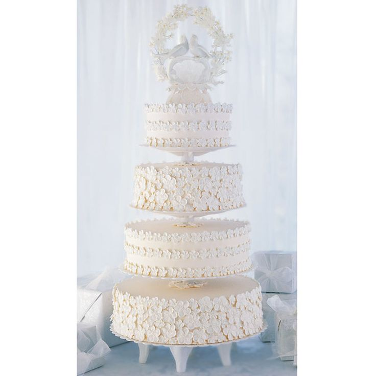 A large wedding deserves a cake worthy of an impression, and this Floral Tones Elegant Wedding Cake is sure to fit the bill. With four tiers of cake and a lovely springtime cake topper, this lovely ivory wedding cake would be great for either summer or spring weddings. Plus the blooming floral borders on each cake layer add a touch of texture and style to this beautiful wedding cake design. A simple cake for experienced decorators, this Floral Tones Elegant Wedding Cake is sure to be a…