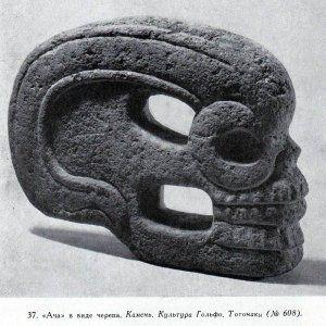 «АЧА» с изображением оголенного черепа с просверленным глазом; линии его сильно стилизованы. Культура Гольфо (тотонаки). Найдена на побережье Мексиканского залива. Базальт.