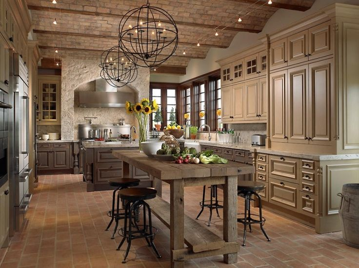 A French country kitchen with an imposing stone enclosure around the stove. The cabinets are painted in muted shades of beige and brown. An adjacent plank table with four stools acts as both a breakfast area and an additional preparation area, if needed. True to French country design, this kitchen accents the natural materials with sunflowers in a glass vase on the table and smaller yellow bouquets in front of the windows above the sink…