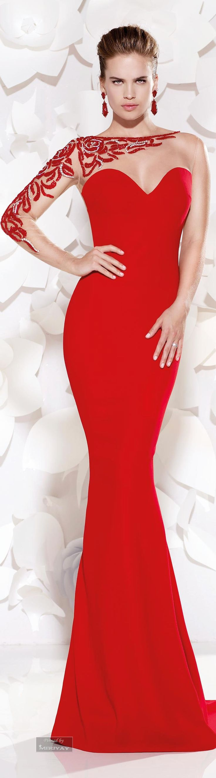 Well, this is the nicest embellishment, I have seen along a neckline, and 3/4 of one arm. The other are is sleeveless. This gown, is also in brightest orange, I have ever seen. I love it. The total body fitting gown travels down the body to a mermaid flare at the knees. Significant, and Stunning !!!
