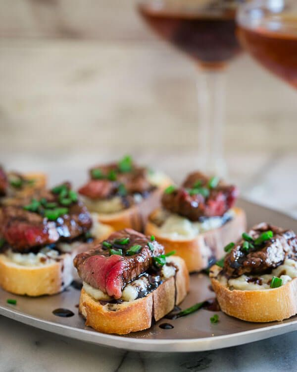 These blue cheese steak crostini are the perfect little bite. Garlicky toasted bread topped with salty blue cheese, rare steak and a balsamic reduction are a great New Year's appetizer.