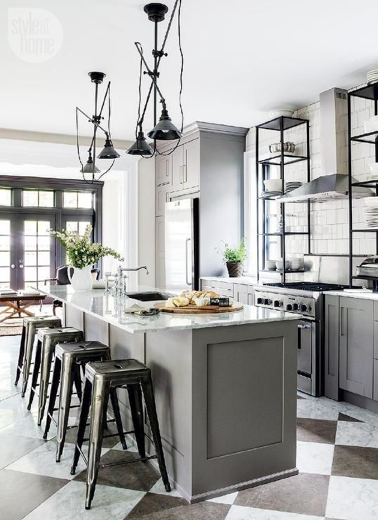 Beautiful kitchen features a pair of vintage swing-arm pendants illuminating a gray center island ...