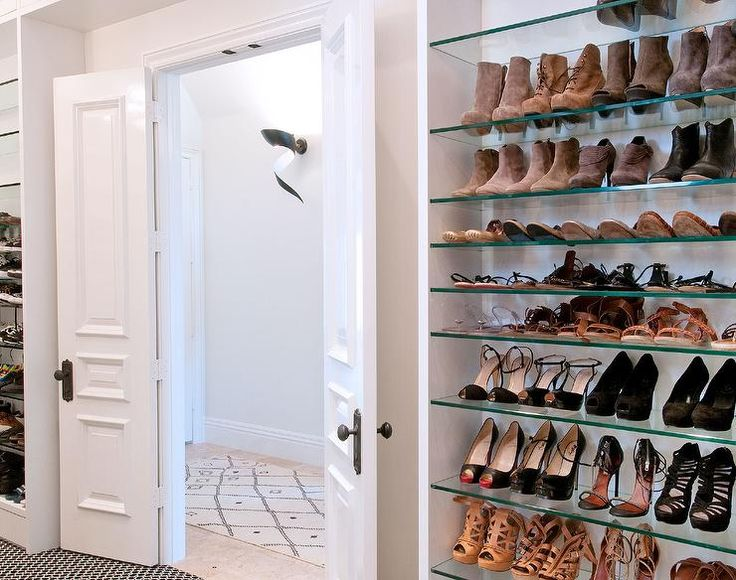 White Paneled Bi Fold Doors Open To A Walk In Closet Flanked By Tall Glass
