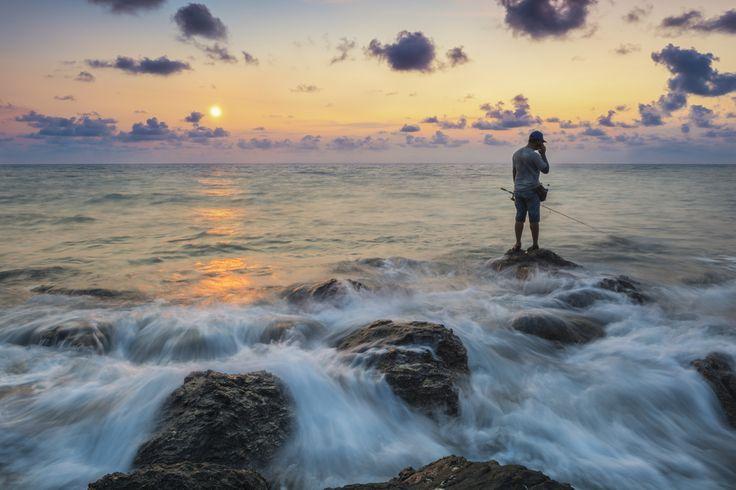 Man fishing in last rays of sunlight on sea shore,Thailand by Chalermchai Karasopha on 500px