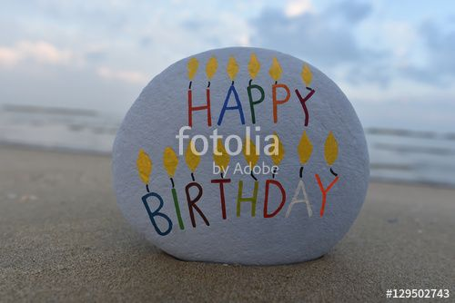Happy Birthday message on a carved and colored stone on the beach