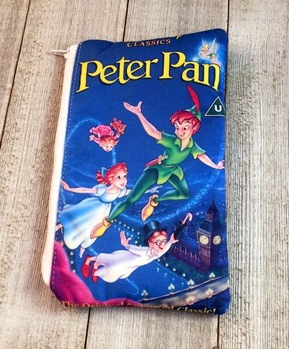 Celebrate the magic with this Peter Pan inspired Zippered Pouch The fabric is made to look like the classic Peter Pan VHS clamshell cover The pouch measures 8x5 and perfect for storing all your small needs, such as money or pens