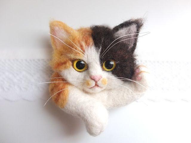 ご閲覧いただきありがとうございます!羊毛フェルトで制作した猫ブローチです。お色は三毛猫さん。 寝転んでくつろいでいる姿をイメージしています。・目の制作時に蓄光パウダーを混ぜ、暗いところで光るようにしました。写真5枚目はUVライトに1分ほど当てたものです。...