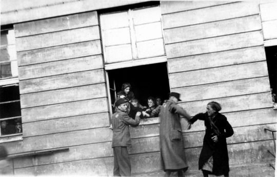 Two Jewish Ghetto Police of the Łódź Ghetto try to remove young children that were hidden in a building during a deportation roundup struggle with Jewish civilians trying to prevent them from taking the children. Jewish Ghetto Police were the auxiliary police units organized in the Jewish ghettos by local Judenrat councils under orders of the occupying Germans. The Judenrat  councils were a widely used administrative agency imposed by the Germans predominantly within the German-created…