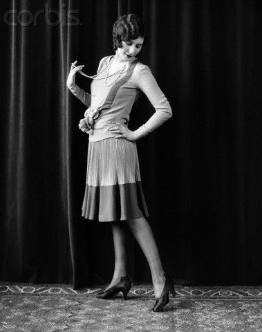 1920s Flapper Woman Posing Hand On Hip Holding String Of Pearls Stretching Leg Checking Hosiery Seams  Photographer: H. Armstrong Roberts  Date Photographed: May 18, 1927