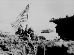 """First flag on Guam on boat hook mast. Two U.S. officers plant the American flag on Guam eight minutes after U.S. Marines and Army assault troops landed on the Central Pacific island on July 20, 1944."""""""