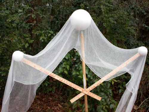 a diy halloween ghost is draped with gauze for a spooky front yard decoration - Scary Homemade Halloween Yard Decorations