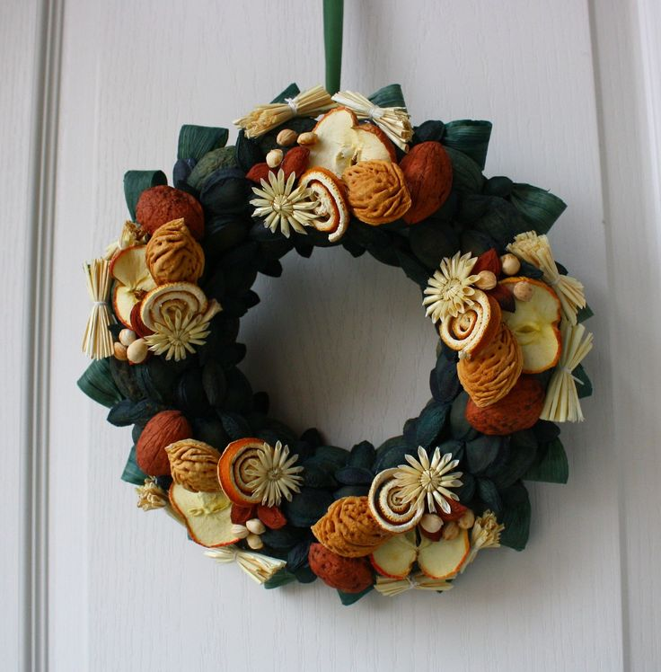 Vítací věnec zelený s jablíčkem Ozdobný věnec z tónovaných přírodních materiálů s náznakem přicházejících vánoc. Je vyroben ze skořápek oříšků, pecek, trávy, slámy, sušených jablek, pomerančové kůry, šustí, čilimníkového proutí a lýka. Upevněn je na pevném slaměném korpusu. Korpus je obalen batikovým papírem. Ze zadní strany je poutko na zavěšení. ...