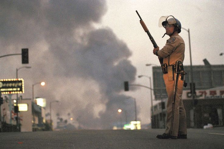 <p>A California Highway Patrol officer stands guard at Ninth Street and Vermont Avenue in Los Angeles as smoke rises from a fire further down the street, April 30, 1992. It was the second day of unrest in Los Angeles following the acquittal of four Los Angeles police officers in the Rodney King beating case. (Photo: David Longstreath/AP) </p>