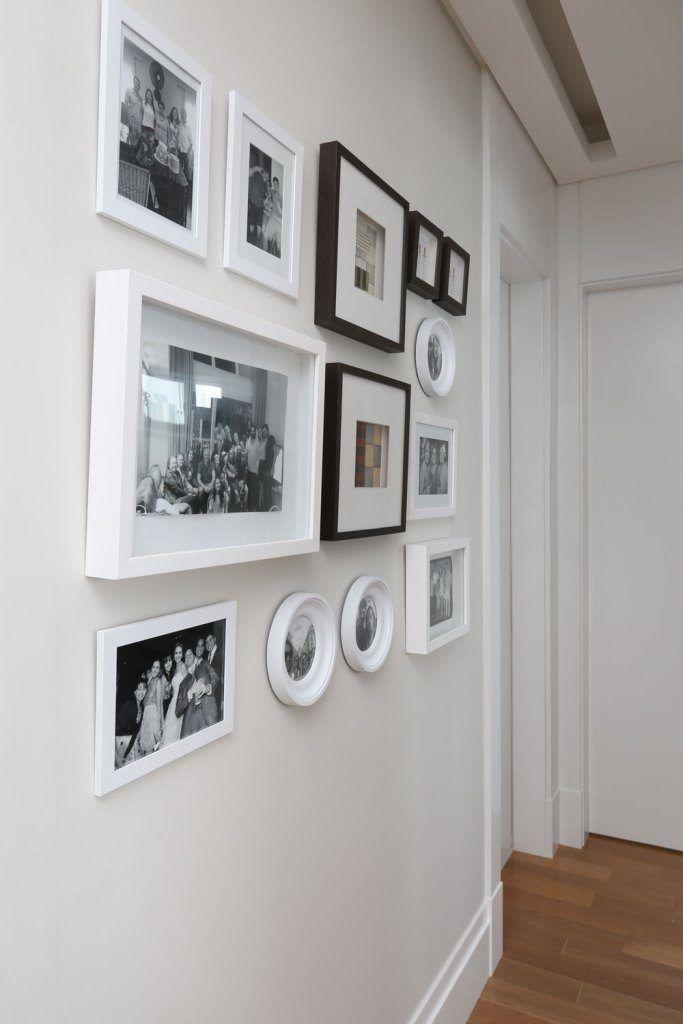 Corredor com monduras para fotos da familia, molduras pretas e brancas. Forro de gesso com rasgo para iluminação indireta. Rodapé branco e piso de madeira. Blog : Danyela Corrêa | Arquitetura e Interiores