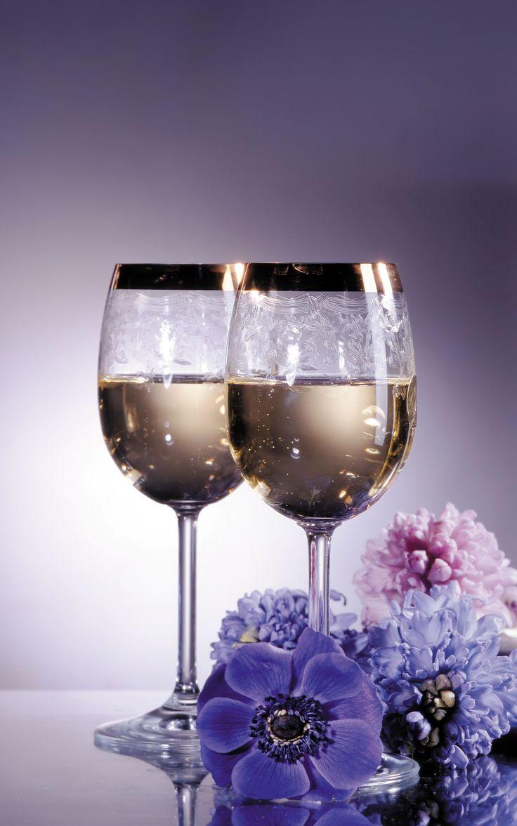 Фото Два бокала с шампанским стоят около композии цветов