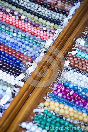 Close view of wooden shelf with rows of colorful beaded strings with price tags on the flea market. Shallow depth of field.