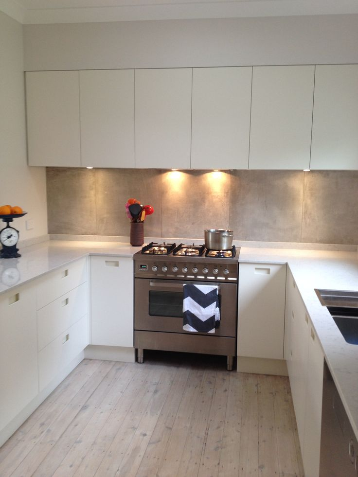 Recessed handles, silestone lagoon bench top, concrete look splash back, white washed floors