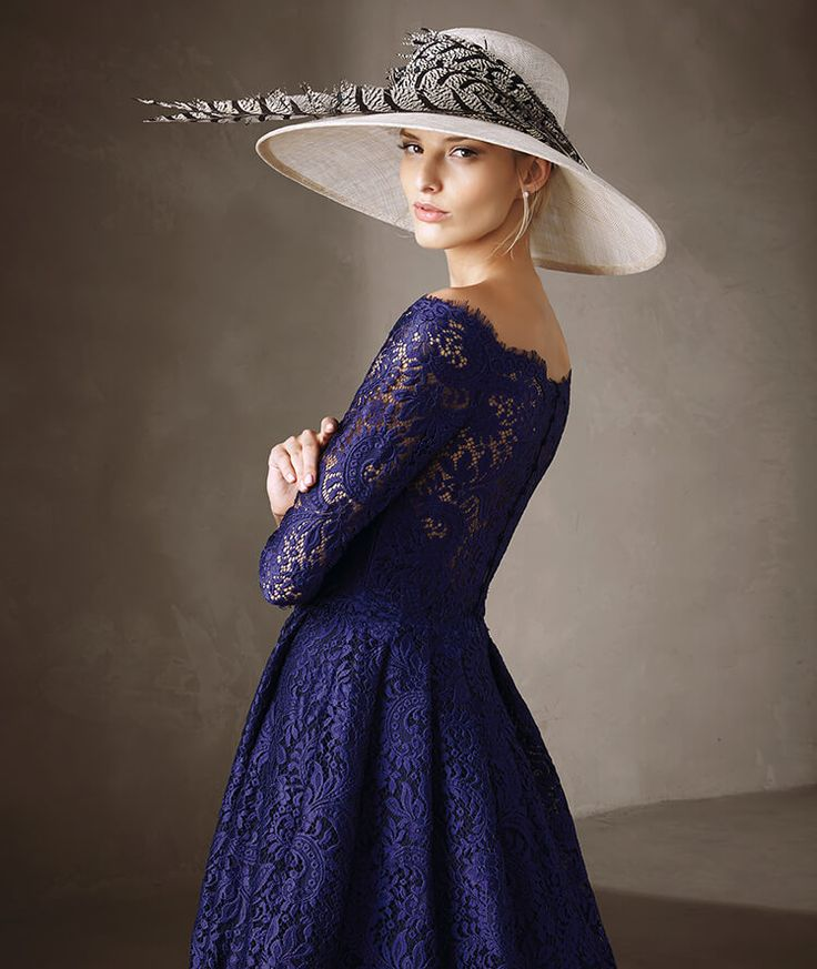 Pronovias > Elegant knee-length dress with 3/4 sleeves and bateau neckline. The dress is covered in lace and the floral motifs give it a special texture. The skirt is fitted at the waist and flares slightly at the bottom.