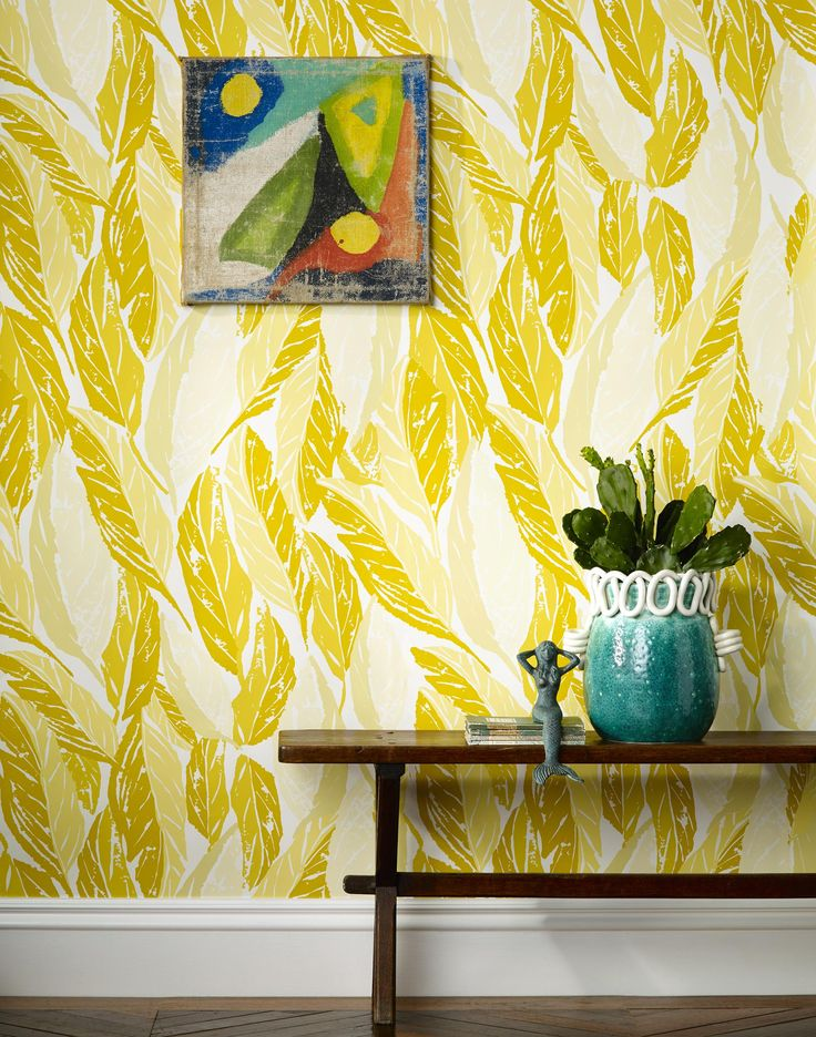 "Wallpaper by Justina Blakeney for Hygge & West. Color: Shades of golden yellow leaves on an off white background. Nana was inspired by the regal leaf of the banana tree. The large leaf motif is meant to provide a lush, jungle-like look that feels simultaneously graphic and organic. Justina's daughter calls bananas, ""nanas""- thus the name."
