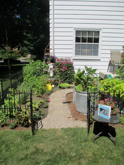 this small vegetable garden with gate and curving pathway packs a lot into a tiny space