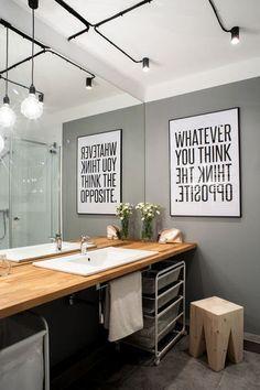 壁に飾ったパネルやさりげなく置かれたイス、天井のライトなどにもこだわりを感じるスペース。シンプルな収納ワゴンも洗面台下にすっきり収まっています。大きなミラーには空間を広く見せる効果も☆