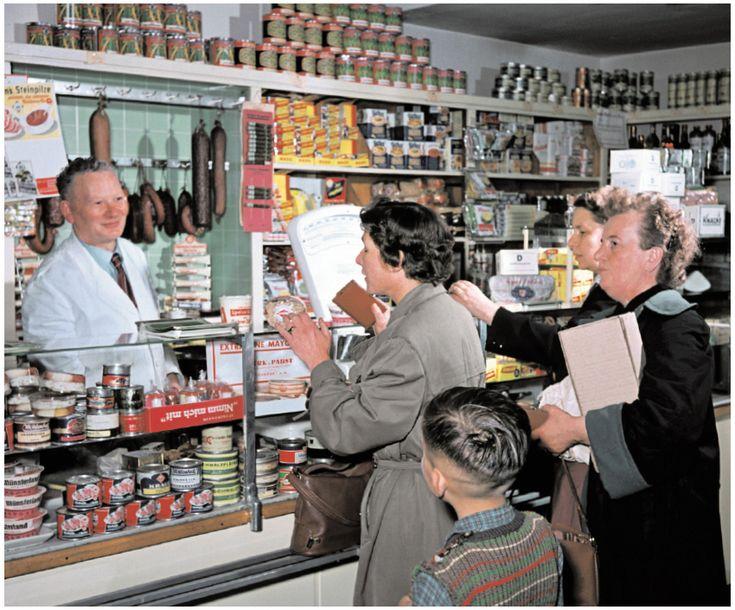 Einkauf beim Kaufmann: Jeder Suppenwürfel wird einzeln begutachtet und über die Theke gereicht. Die Wartenden bilden Chor und Publikum zugleich. Man kennt sich, man trifft sich, man schwätzt miteinander. In Bonn 1956.