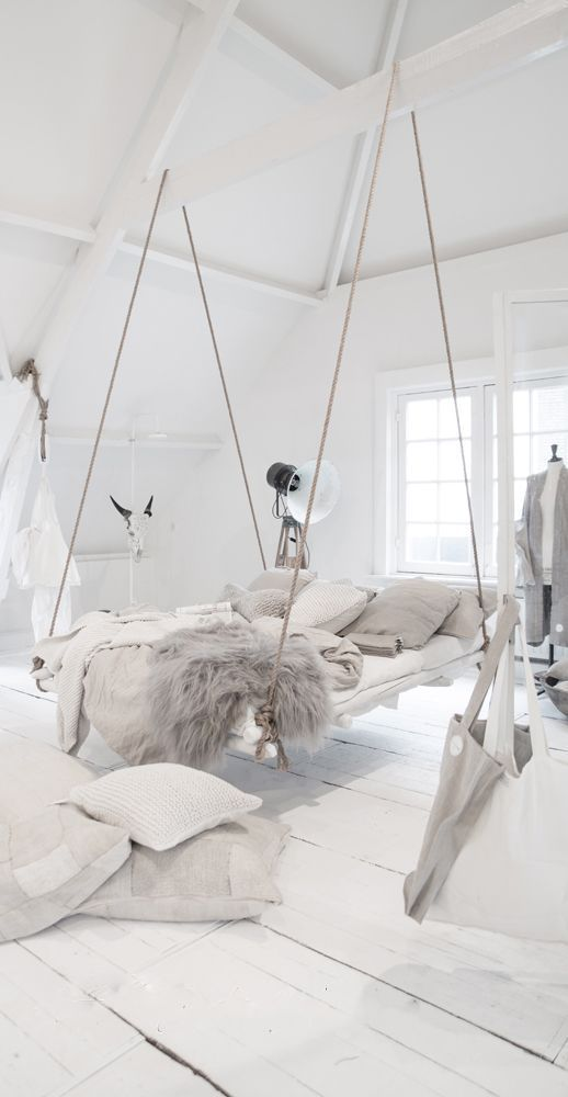 Incredible hanging bed idea in an all white bedroom with lots of cozy blankets and pillows.