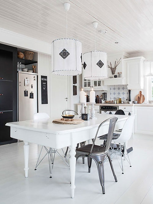 Big white Scandinavian kitchen w/ a lovely white painted table n the center.