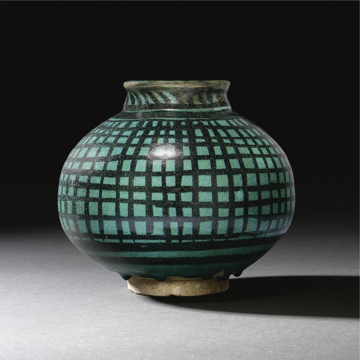 A RARE RAQQA TURQUOISE-GLAZED JAR, SYRIA, EARLY 13TH CENTURY the frit body of compressed globular form on a short narrow foot, with everted rounded rim, painted in underglaze black with a turquoise glaze, the body with a hatched design of vertical and horizontal stripes, minor and major bands above and below 20.4cm.