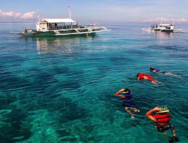 People snorkelling in the foreground, boats in the background