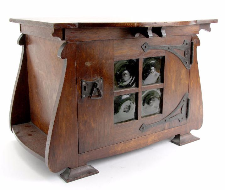 English, Art Nouveau, early 20th century oak smoker's cabinet, bow fronted top above a cupboard door with rustic style iron hinges and handle, with four crown glass plates with pontil scars, the interior fitted with two drawers and shelves, raised on moulded bracket feet, 43cm wide, 30cm deep, 31.5cm high (16.5in wide, 11.5in deep, 12in high)