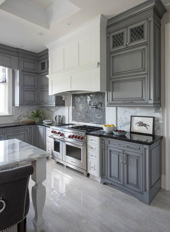 white and gray kitchen features gray wash cabinets paired with black granite countertops and a gray