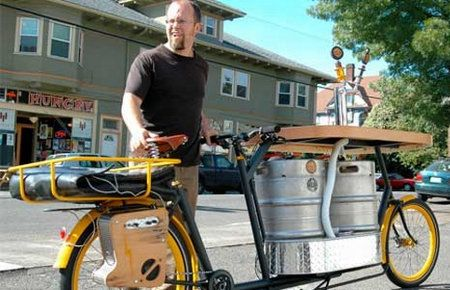 Dude carries 2 kegs and pizza on a bike.